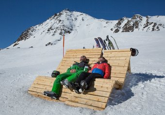 Skiers taking a break on a sun bed besides the Paradiso piste, Corviglia
